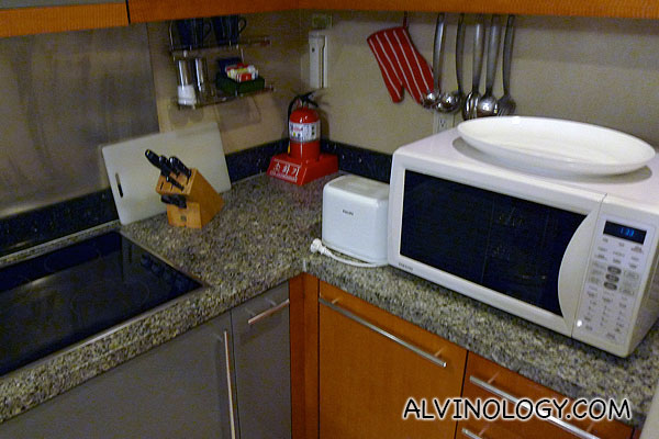 There is a microwave, stove, and full set of cookware and utensils