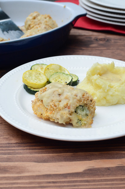 A serving of Broccoli Cheese Stuffed Chicken on a white plate with potatoes and zucchini.