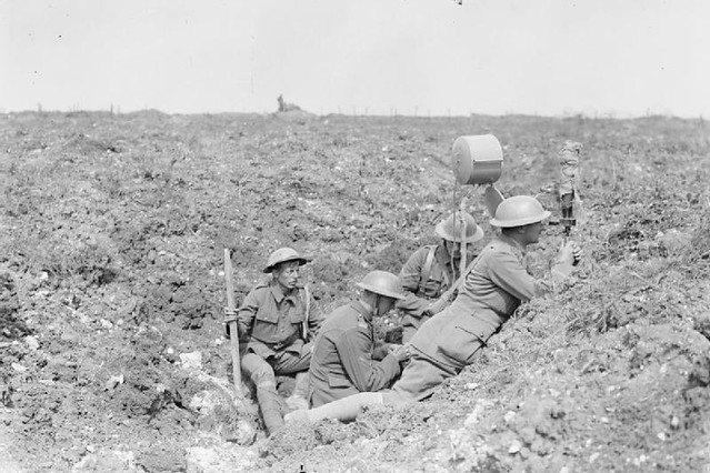 British Royal Garrison Artillery using a daylight signalling lamp in a shell hole in front of Fricourt Wood, September 1916, by John Warwick Brooke