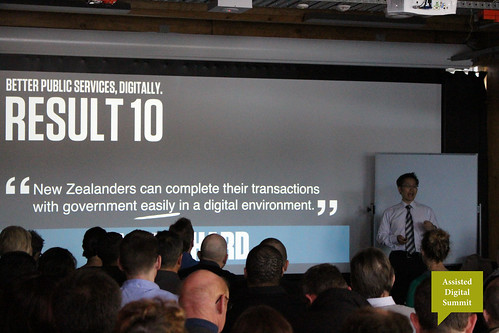 "A photo of Richard Foy giving a presentation with the words ""Better Public Services Digitally - Result 10:  New Zealanders can complete their transactions with government easily in a digital environment"" on screen behind him"