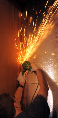 Sparks fly as Adam saws off the screws for an even surface,  power saw, gloves, protective glasses, renovation, closet, insulation, Seattle, Washington, USA by Wonderlane