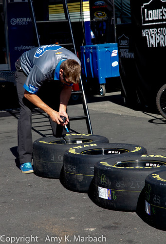 Crew member works on tires