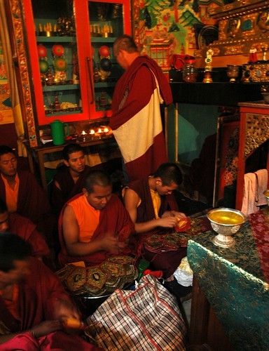 Preparing the 5 Dhyani Buddhas crowns for initiation, offering saffron water, western meditator Steve (wearing an adi) gazes at a side shrine, monks, Tharlam Monastery of Tibetan Buddhism, Boudha, Kathmandu, Nepal by Wonderlane