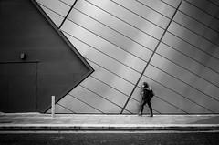 Girl walking beside modern building
