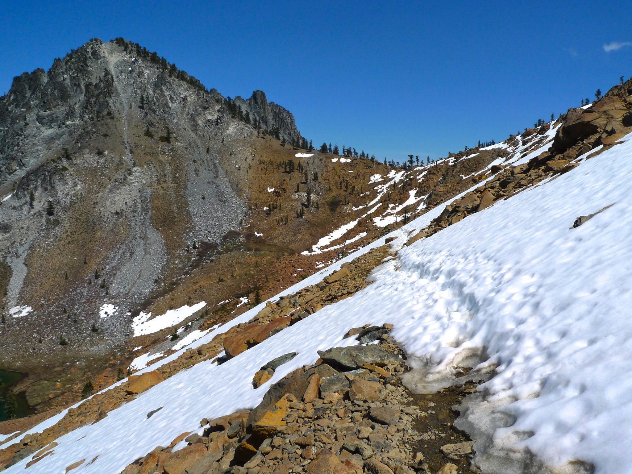 The trail to Summit Lake from Deer Pass is north facing and holds snow longer than elsewhere. I was crossing in the afternoon, which made for slow going as I kicked through thin crusts to solid footing of the rocks below. I didn't want to step and punch t