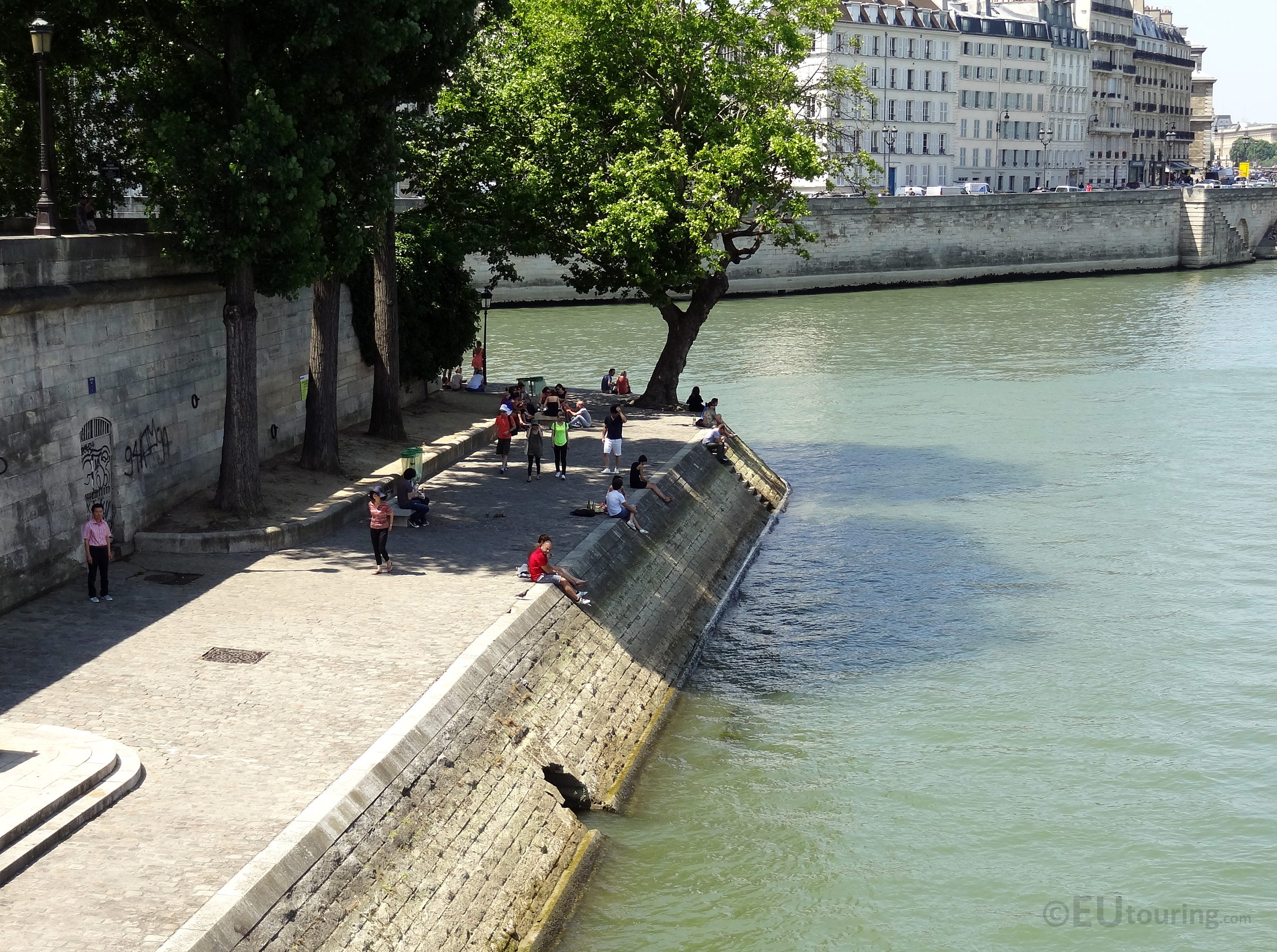 People relaxing beside the river