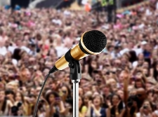 Image of microphone with large audience in background