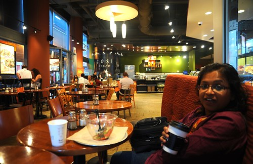 Co-worker Monalisa holding a paper cup of coffee, salad bowl, tables, lights, cafe, COSI Bread Restaurant, Chicago, Illinois, USA