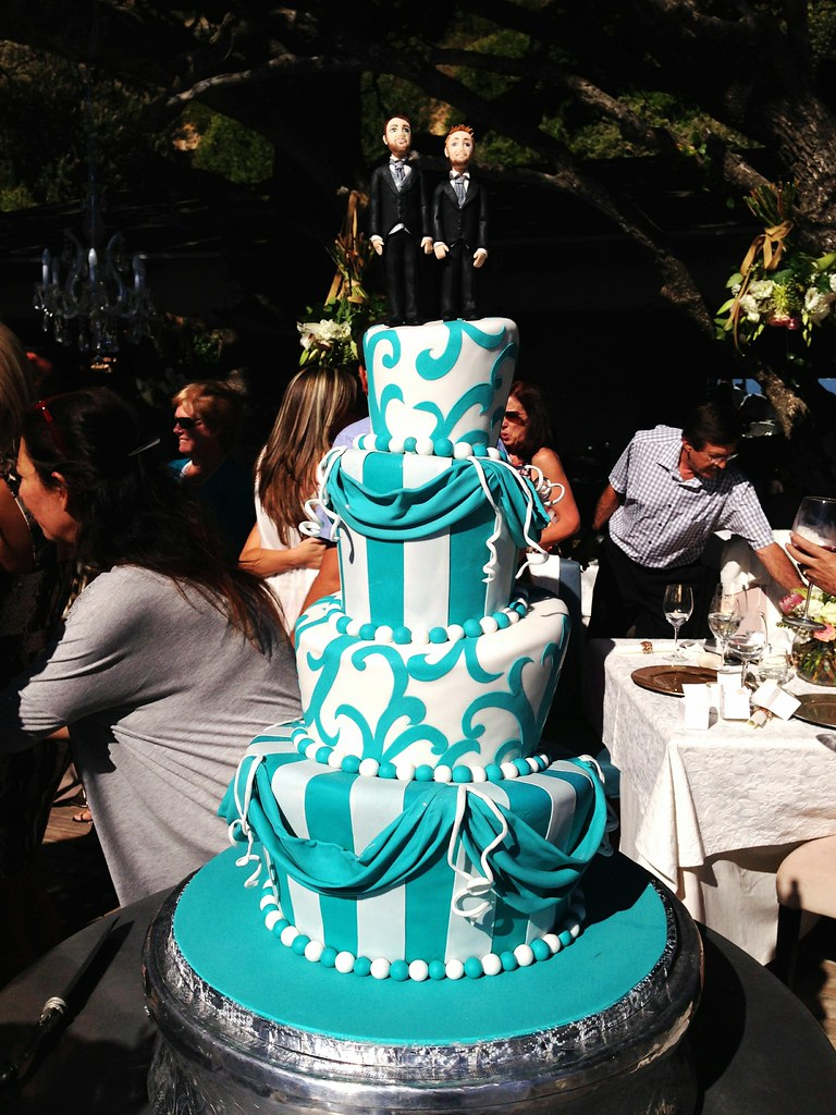 4-tier Mad Hatter style wedding cake in bright teal and white, with ...