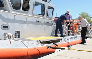 Coast Guard Petty Officer 2nd Class James Summers, a crewmember at Station New Haven, help an open house attendee onto a small boat for a tour at Coast Guard Sector Long Island Sound's open house hosted in New Haven, Conn., May 17, 2014. Sector crews hosted the open house event for all ages, which included boat tours, safety demonstrations, important boating safety tips from the Coast Guard Auxiliary and interactive displays form partner emergency response agencies. (U.S. Coast Guard photo by Petty Officer 3rd Class Michael Himes)