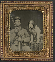 [Unidentified soldier in Confederate uniform with shotgun sitting next to dog] (LOC)