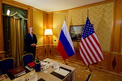 U.S. Secretary of State John Kerry waits by a set of U.S. and Russian flags on December 2, 2016, at the Parco dei Principe Hotel in Rome, Italy, before a bilateral meeting with Russian Foreign Minister Sergey Lavrov on the sidelines of an Italian-hosted multinational meeting focused on Mediterranean issues. [State Department photo/ Public Domain]