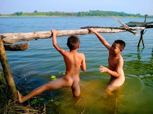 Two boys naked at the swamp in a small village.