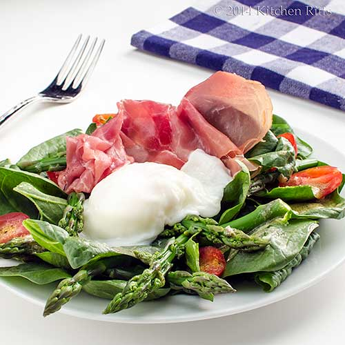 Asparagus and Spinach Salad topped with prosciutto and a poached egg