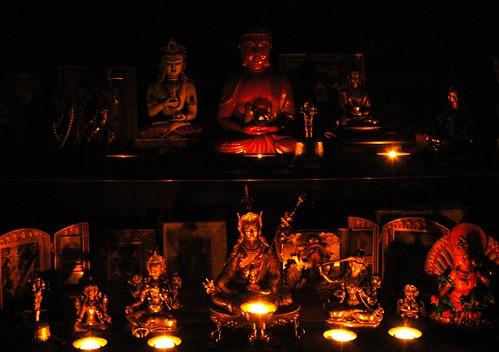 Buddhist Shrine lit with candles, from left to right, bottom to top, Vajra bell, Tara, Tara, Padmasambhava, Manjushri, Vajra Guruda, Zambala, Vajrayogini, Vajrayogini, Vajra Sattva, Amitabha Buddha / Gyalwa Gyamtso, vajra bell, Lord Buddha, Padmasambhava, by Wonderlane