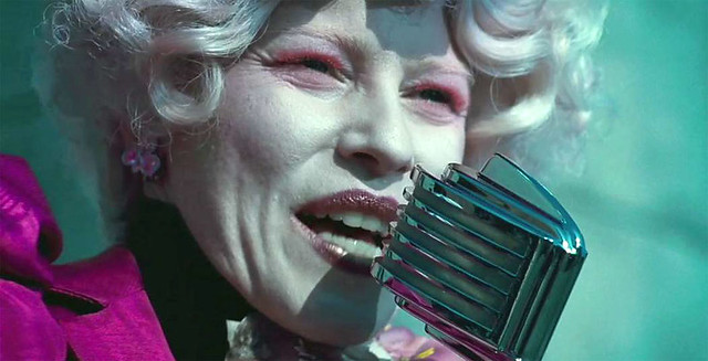 Effie, from the Hunger Games, wearing thick white makeup and purple lipstick