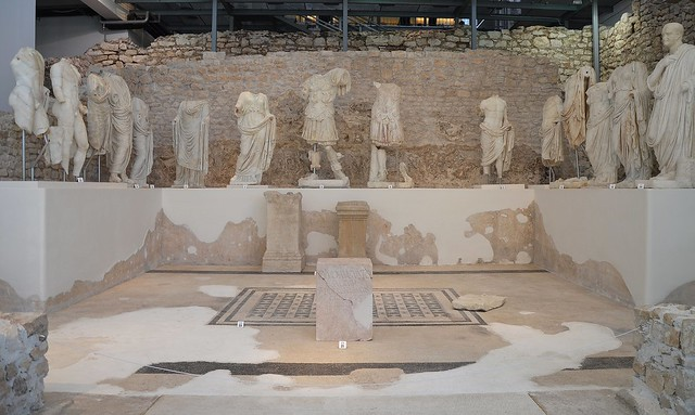 The remains of the Augusteum and fifteen marble sculptures exhibited on a platform, Archaeological museum Narona, Vid, Croatia
