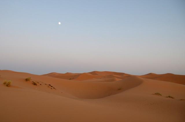 Sale la luna en el desierto tras el atardecer en el Sahara