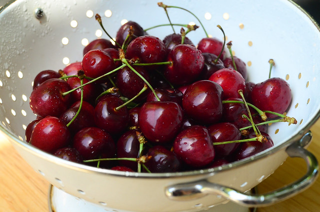 A colander full of cherries being washed.