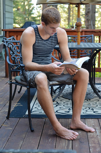 A young man sitting in a chair on a deck reading a book.