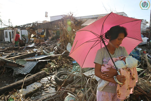 A woman holds her baby amid the wreckage of Typhoon Haiyan