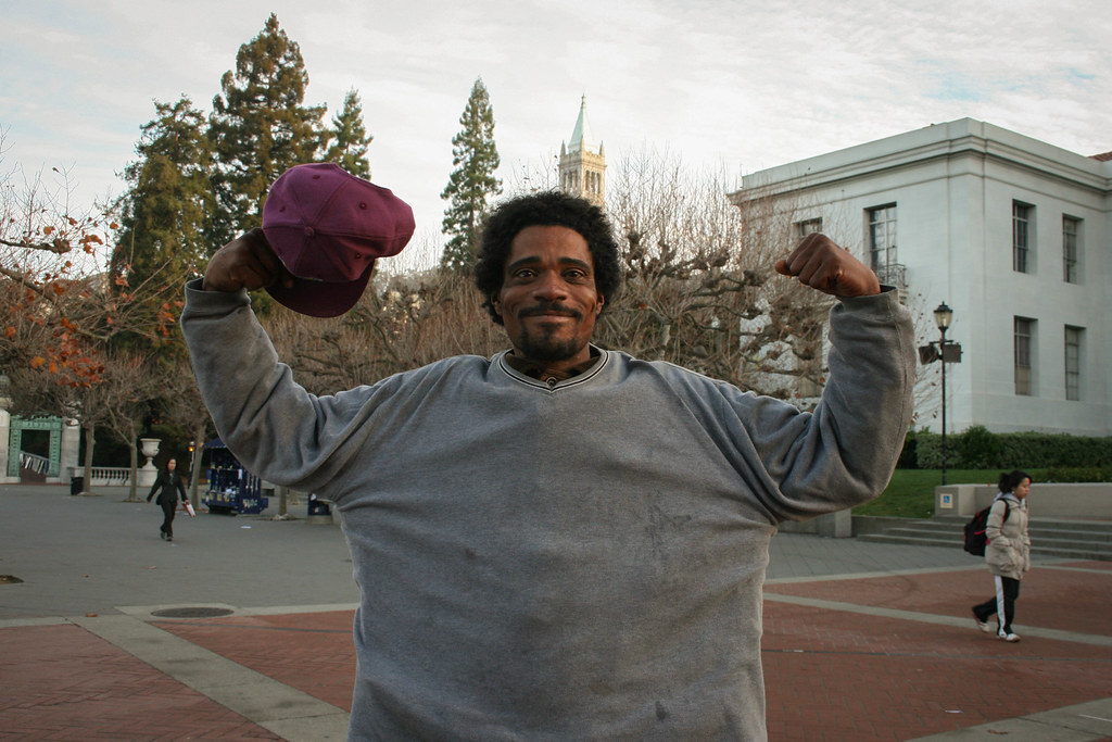 Homeless man striking a pose on the UC Berkeley campus.