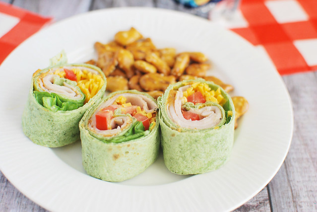 Zesty Turkey Roll-Ups - deli turkey, cheddar cheese, tomatoes, lettuce, and taco seasoned mayo rolled up in a spinach wrap! Perfect for lunchboxes!