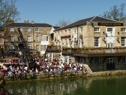 Crowded courtyard outside the Head of the River pub with the River Thames in the foreground