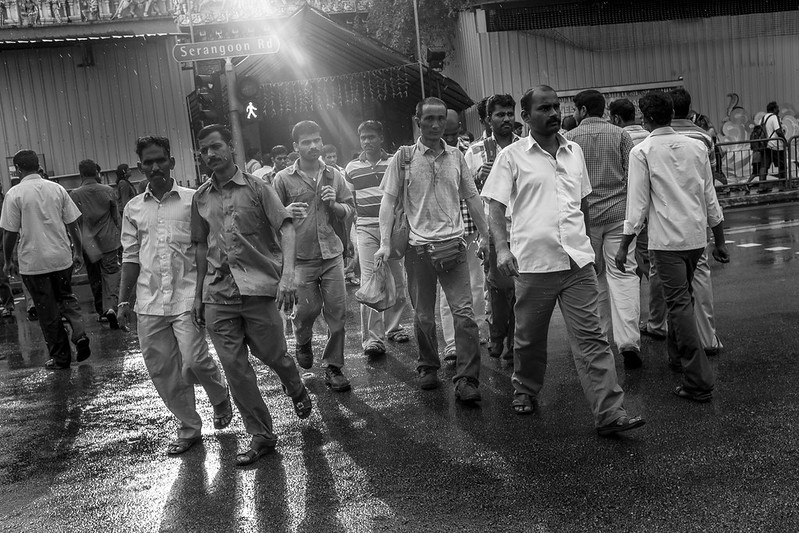 Men crossing the road from an Indian temple along Little India in the late afternoon sun after a drizzle.