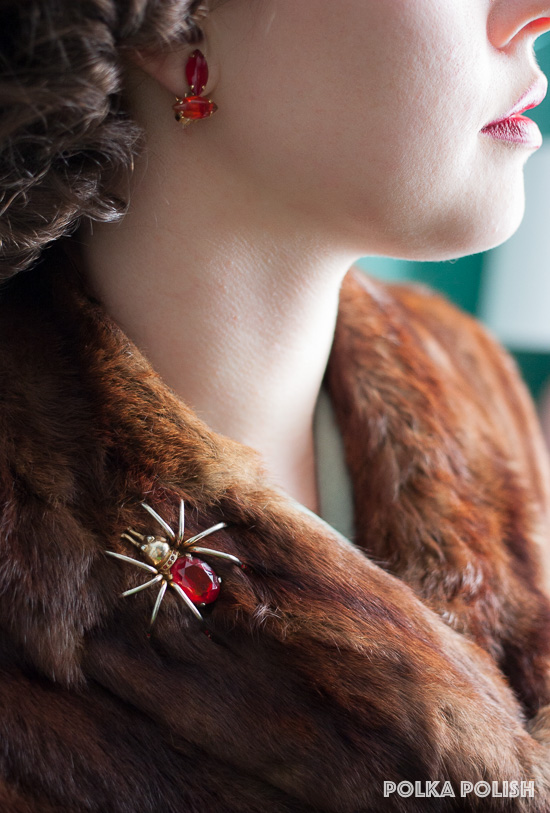 Red earrings and a bold red spider brooch stand out against a warm mahogany brown fur collar
