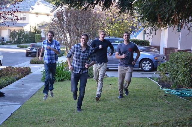 Four young men run across a lawn towards the camera.