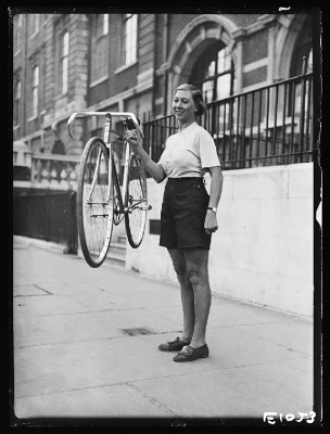 Woman holding a lightweight bicycle, 1934 - 5