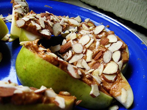 sliced almonds on peanut butter pears