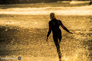 young girl splashing at sunset on a california beach