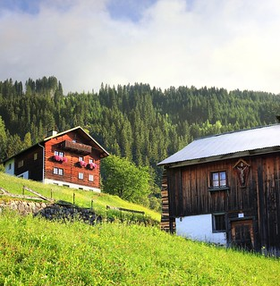 Typical Tyrolean houses with a small sanctuary on the steep mountain hills