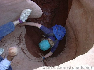 My dad helps me over a mudhole and up a dryfall in Peek-a-Boo Slot Canyon, Grand Staircase Escalante National Monument, Utah
