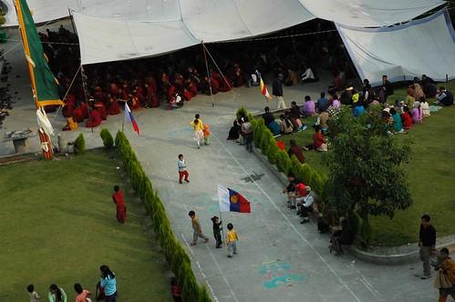 Tibetan children playing, claim this place for Buddhism with the International Buddhist flag, overflow monks, nuns, and lay people under the tent, tall prayer flag, Sakya Lamdre, courtyard, Tharlam Monastery of Tibetan Buddhism, Boudha, Kathmandu, Nepal by Wonderlane