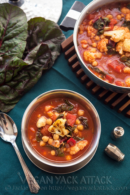 A bowl of Roasted Cauliflower Tomato Soup next to a large pot of soup and chard