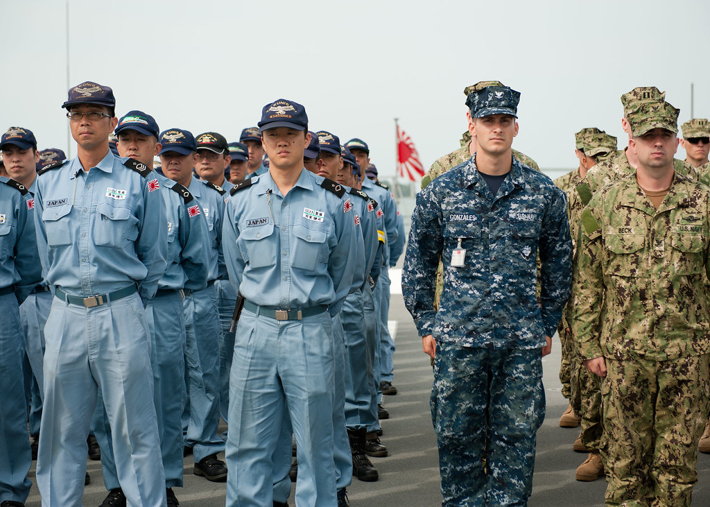 U.S. Navy and Japan Maritime Self-Defense Force sailors stand in formation.
