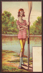 Man with monocle and bathing costume standing with an oar by the water. [front]