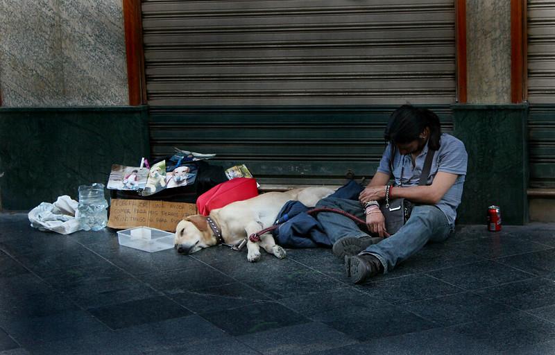 Un hombre con su perro, en el centro de Sevilla, pidiendo dinero para ganarse la vida.