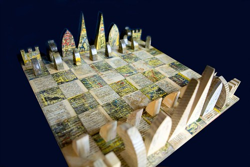 Chess set made of compressed yellow pages and unread books