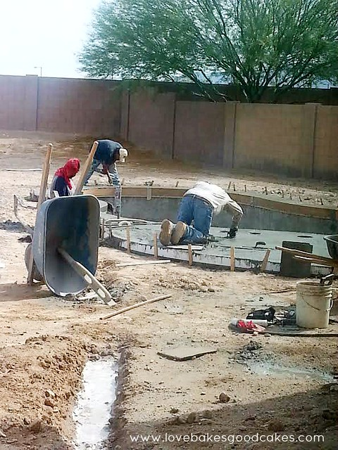 Men finishing the construction of a swimming pool.