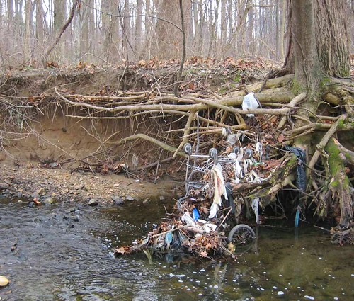 Image of a degraded, eroded stream.  Trash and debris are on the stream side and the side of the stream have eroded away