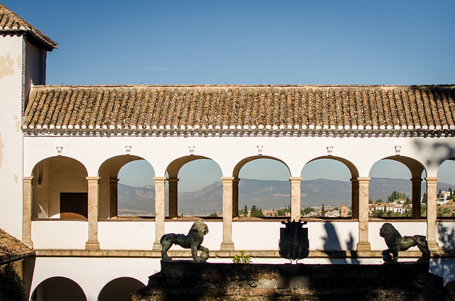 The arched walkway over the Generalife Palace offers breathtaking views of the Sierra Nevada mountains and the city of Granada.