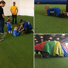 This is what 18-24 month olds playing soccer really looks like: playing under a parachute, getting hand stamps and lying on the ground when you're feeling like it's break time.