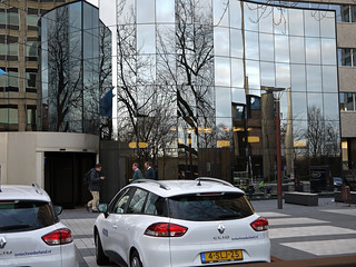 Close-up photo of reflecting windows of an office-building and people leaving the office a 4 o'clock - on the forground cars in front of the facade - near Amstel-station / Omval / Spaklerweg in Amsterdam city; - urban photography by Fons Heijnsbroek, 2013
