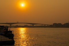 Sunset over the Krungthep bridge seen from Asiatique - The riverfront by the Chao Phraya river in Bangkok, Thailand