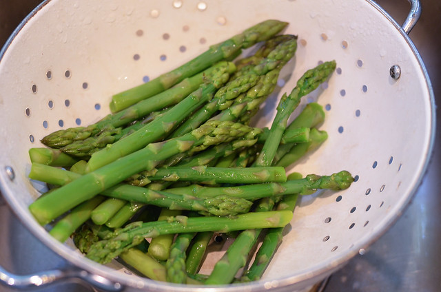 Cooked asparagus in a colander.