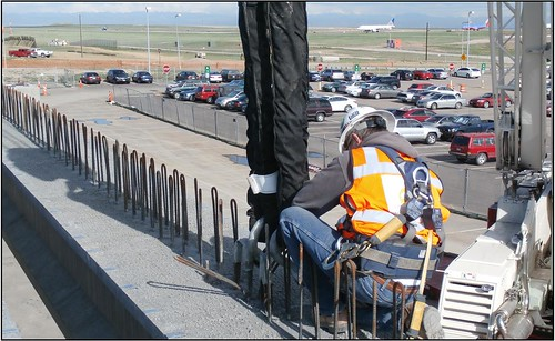 Photo of worker placing concrete girder on bridge over airport employee parking lot